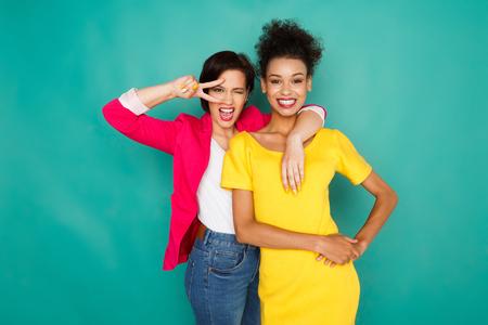 amistad multiétnica y concepto de apoyo. mulata y caucásicos en ropa casual feliz que presenta y que se divierte en el estudio de fondo azul con espacio de copia