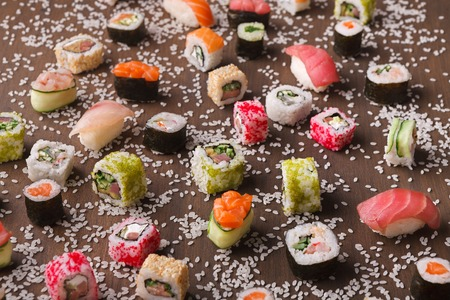 Japanese food restaurant delivery - sushi maki california roll big party platter set with sesame on wooden rustic background, above view