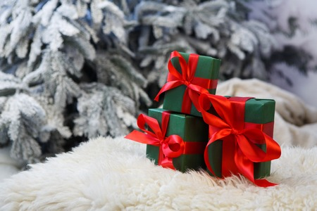 red carpet background: Christmas gifts decorated with red ribbon bows on soft fluffy carpet at blurred snowy fir tree background, closeup, selective focus. Winter holidays concept