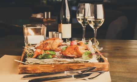 Romantyczna kolacja w restauracji dla smakoszy. Przepiórki ze szparagami i kurkami podawane na nieczystym drewnianym talerzu, kieliszkach do wina i świecy na stole. Ekskluzywne posiłki dla smakoszy, kopia przestrzeń
