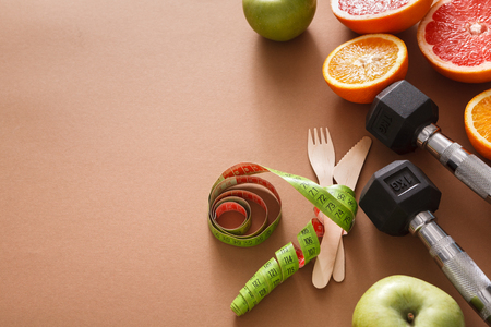 Healthy eating and slimming background copy space. Tape measure wrapped around knife and fork with dumbbells and fruit top view. Diet, weightloss concept