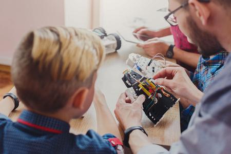 Stem education. Kids creating robots with teacher, back view. Early development, diy, innovation, modern technology concept