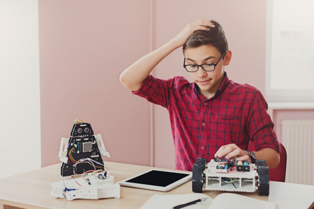 Stem education. Embarrassed boy made mistake while creating robot at lab, looking at blank tablet screen. Early development, diy, innovation, modern technology concept Banque d'images