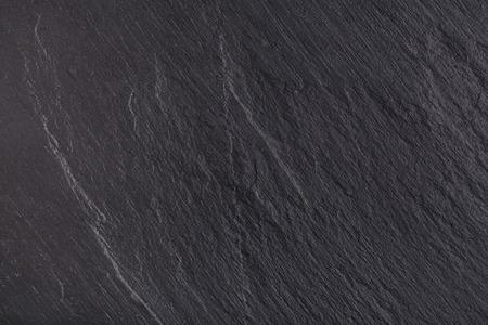 素朴な黒スレート石背景。暗い質感