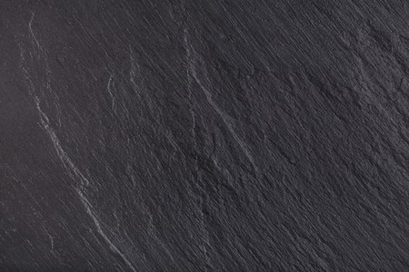 Rustic black slate stone background. Textured dark surface