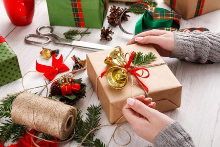 decorating: Creative diy hobby. Decorating modern handmade xmas present with bells. Box in craft paper with red green checked ribbon. Womans hands on white wood table with fir tree branches, decoration of gift.