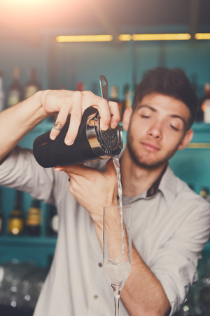 adding: Young handsome bartender in bar interior pouring alcohol cocktail drink into glass. Service industry occupation. Stock Photo