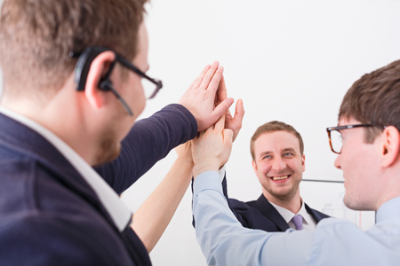 Closeup of succesful people in suit in office, young businessmen and women unite hands for teamwork and cooperation. Made a plan. White background Stock Photo