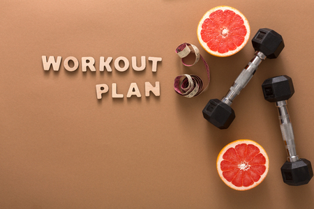 Workout plan and slimming tools copy space. Wooden words with dumbbells, measuring tape and grapefruit on brown background