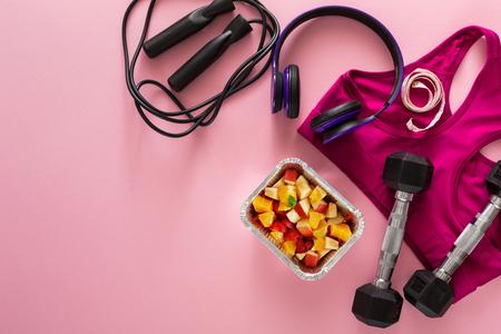 Abbigliamento ed attrezzature femminili di sport con la vista superiore dell'insalata di frutta, spazio della copia. Set di nuovi completi fitness per donna, alimentazione sana, stile di vita attivo, concetto di cura del corpo