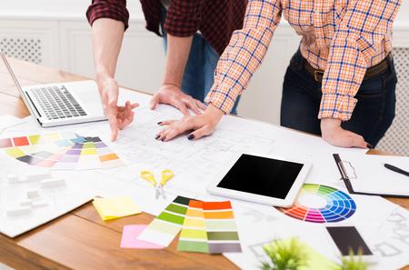Team di designer professionisti irriconoscibili che lavorano al progetto, discutendo della creazione di spazi funzionali, idee di decorazione, scelta di combinazioni di colori