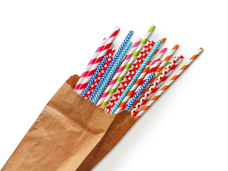 Colorful striped party cocktail straws in craft paper bag isolated on white background. Bright plastic pipes