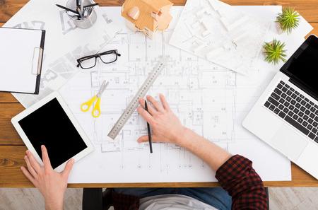 Architektenzeichnung auf Architekturprojekt. Draufsicht über unerkennbare Designerhände, die mit Gebäudeplan, leerer Tablette und Laptopschirm, Modell arbeiten