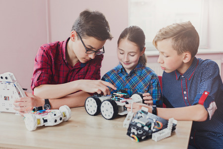 Children creating robots at school, stem education, copy space. Early development, diy, innovation, modern technology concept 免版税图像