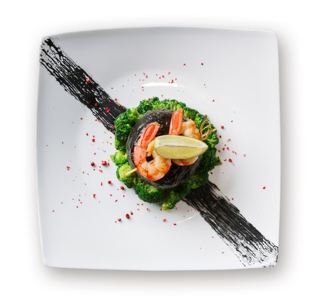 Exquisite restaurant food. Dorado fillet wrapped in nori on broccoli with shrimps and lemon piece on top. Served on white platter, sprinkled with pepper salt, isolated on white background, top view Stock Photo