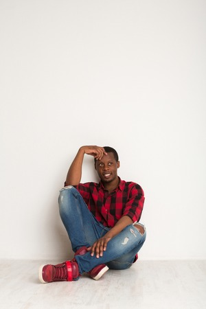 Happy smiling black man sitting with crossed legs, hand on head, at white studio background, man style, copy space Stock Photo