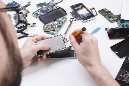 hands free phone: Repairman disassembling smartphone with screwdriver. Technician fixing broken phone, electronics repair service, repairer pov, copy space for text