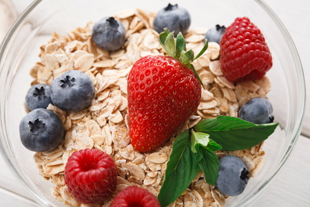 Tasty breakfast with muesli, sweet fresh strawberries, raspberries and blueberries closeup. Low fat morning meals and healthy start of the day. Detox and eating right concept