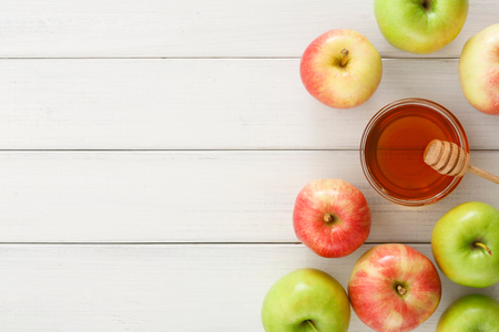 Seasonal autumn background. Honey and lots of ripe apples on white wooden table with copy space, top view