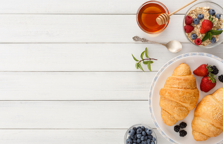 Rich continental breakfast background. French crusty croissants, muesli, lots of sweet berries and honey for tasty morning meals. Delicious start of the day. Top view with copy space on wooden table