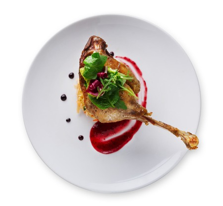 Exclusive restaurant meals. Duck confit with braised cabbage, baked apple and cranberry sauce, isolated on white background, top view