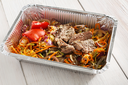 Healthy lunch, take away meals in foil container, steamed meat with salad. Fitness nutrition. Restaurant dishes delivery