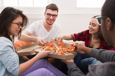 Delivery de pizza. Gente feliz almorzando en la oficina de coworking durante el descanso, cultivo, primer plano
