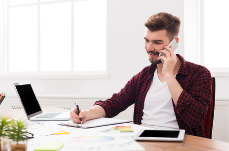 Important call. Young smiling businessman in casual talking on mobile phone in modern white office interior.
