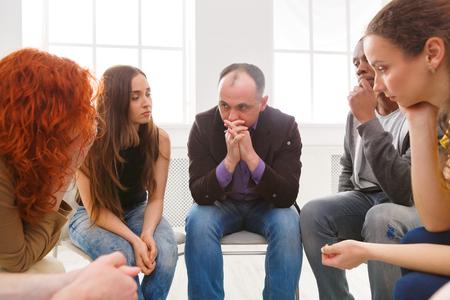 Bijeenkomst van steungroep. Depressieve man zit aan rehab groepstherapie. Psychotherapie, depressie, leven problemen concept Stockfoto - 87719453