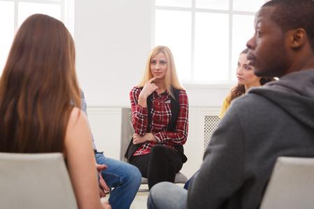 支援グループの会合。若い女性セラピストが他の人に聞いて。メンタルヘルス、心理療法の概念 写真素材