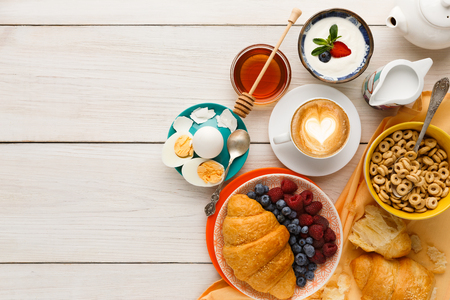 Rich breakfast menu background. French crusty croissants, muesli, yogurt, coffee, berries, honey and boiled eggs for tasty morning meals on wooden table, top view, copy space Stock Photo