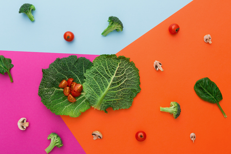 Diet, detox and healthy food concept - top view flat lay of fresh organic raw vegetables on abstract bright background. Ingredients for salad - broccoli, mushroom, carrot, cherry tomato, spinach