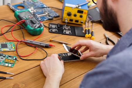 Unrecognizable man disassembling smartphone in repair shop. Repairman separating mobile phone parts for diagnostics
