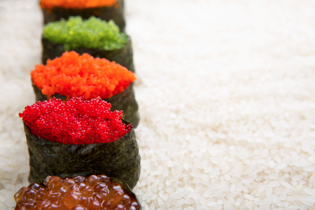 granule: Closeup of sushi gunkan with colored caviar on white rice background and texture copy space