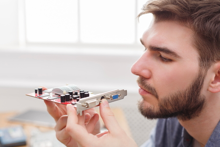 Programmer studying broken video card in workshop. Young repairman examing computer motherboard to find crash, closeup Stock Photo