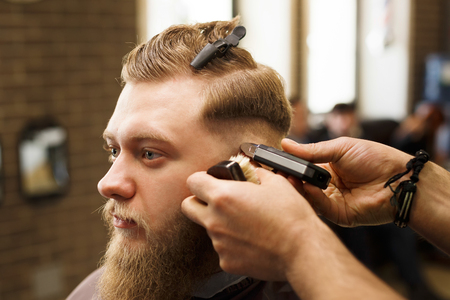 Barber styling beard with trimmer at barbershop, closeup. Barbershop for men Stock Photo