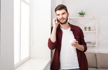 Young man having pleasant conversation on mobile while standing near window at home and drinking coffee, copy space Stock Photo