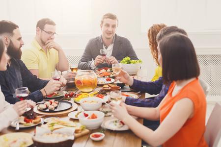 Incontro degli amici Il gruppo di persone beve il vino alla tavola di cena del partito in caffè, ristorante. La giovane azienda celebra con l'alcool e il cibo alla tavola di legno all'interno.