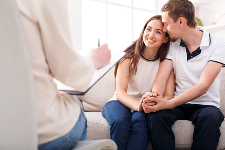 Happy couple reconciling at therapy session in psychotherapists office