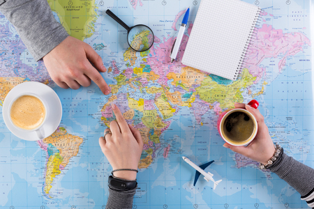 Couple planning airplane trip to Morocco, point on map, taking notes in blank notebook, copy space