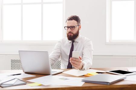 Nadenkend zakenman op het werk. Formele jonge mensenwerknemer die oogglazen draagt ??op het werk met computer, het concept van baanconcepten. Levensstijl portret