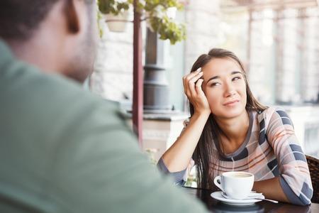 Junges gebohrtes Mädchen, das Kaffee auf Datum mit ihrem Freund am Café sitzt und trinkt. Speeddating, erfolgloses Treffen