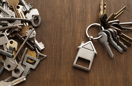 Bunch of keys with house shaped trinklet against wooden background and collection of different keys. Safety, security and real estate concept, top view, copy space Stock Photo