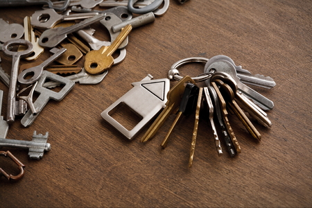 Stelletje toetsen met huis vormige trinklet tegen houten achtergrond en verzameling van verschillende sleutels. Veiligheid, beveiliging en onroerend goed concept