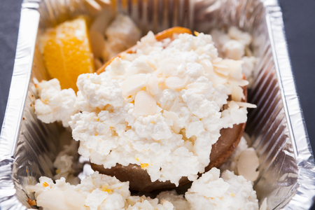 Healthy lunch in foil container, dieting and detox concept. Cottage cheese, persimmon and mandarin, close up Stock Photo