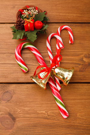 motouz: Sweet christmas background. Traditional candy canes on rustic brown wooden surface with jingle bells and xmas decoration, copy space, top view Reklamní fotografie