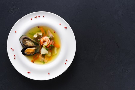 French cuisine restaurant. Seafood soup with white fish, shrimps and mussels in plate sprinkled with spices. Freshly cooked exclusive meals at black background with copy space, top view Standard-Bild