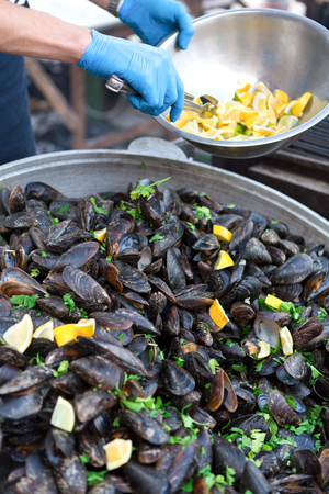 Fresh grilled mussels closeup. Unrecognizable male chef cooking seafood barbeque outdoors, adding parsley and lemon to clams, tasty background. Stock Photo