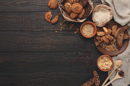 Kookingrediënten voor zelfgemaakte havermoutkoekjes en biscotti. Havervlokken en bloem in houten kommen bij donkere rustieke achtergrond met exemplaar ruimte, hoogste mening. Met de hand gemaakt deegachtig concept en receptenmockup