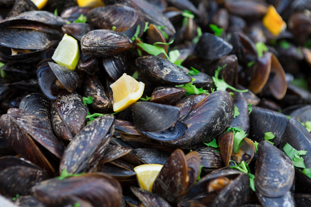 Fresh grilled mussels closeup. Seafood barbeque outdoors, clams with parsley and lemon, tasty textured background.